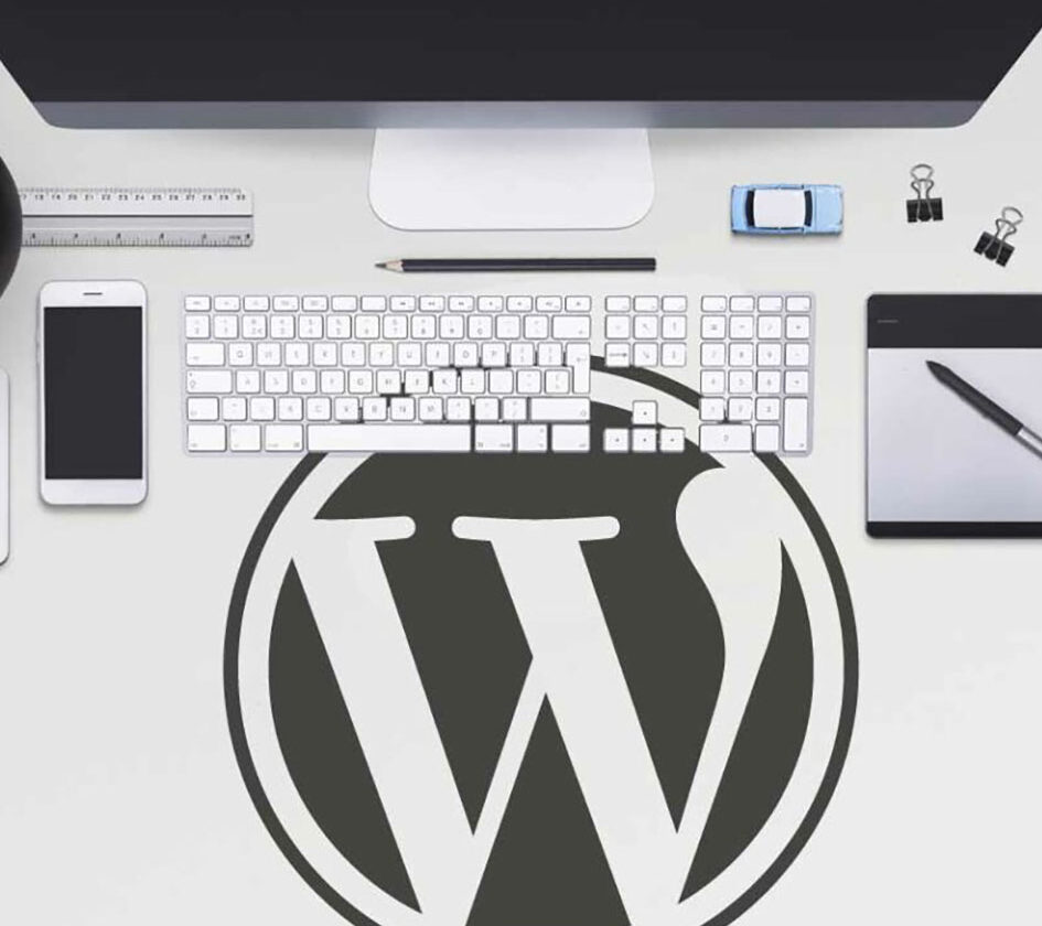 Wordpress logo on computer desk surrounded by keyboard and screen
